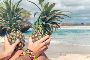 Woman hands with fresh exotic pineapple fruit on the ocean background. Fresh healthy diet food concept. Bali island. Indonesia.