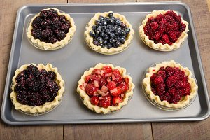 Filled fruit pies on baking pan