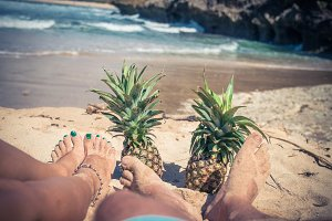 Woman and man legs with pineapples on the beach of Bali island. Indonesia.