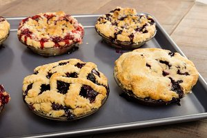 Fresh warm fruit pies on tray