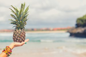 Woman hand with fresh exotic pineapple fruit on the ocean background. Fresh healthy diet food concept. Bali island. Indonesia.