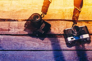 Two vintage film cameras lie on a colorful wooden surface, a color filter