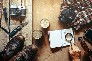 Hiking accessories on wooden background: old hiking leather boots, vintage film camera, travel notebook, knifes. Lifestyle concept adventure vacations outdoor. Flat lay style