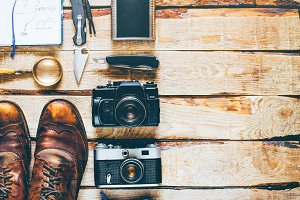 Hiking accessories on wooden background: old hiking leather boots, vintage film camera, travel notebook, knife. Lifestyle concept adventure vacations outdoor. Flat lay style
