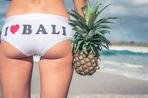 Sexy tropical woman butt close up with exotic pineapple fruit on the beach of paradise island of Bali. Healthy diet concept. I love Bali panties.