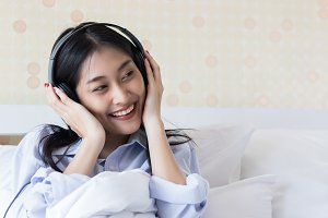 Happy Asian woman on bed