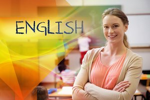 English against pretty teacher smiling at camera at back of classroom