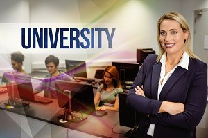 University against computer teacher smiling at camera with arms crossed