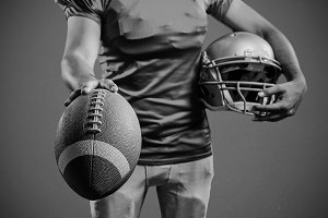 Composite image of mid section of sportsman showing american football while holding helmet