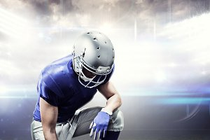 Composite image of american football player kneeling while holding ball