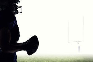 Composite image of side view of sportsman holding football