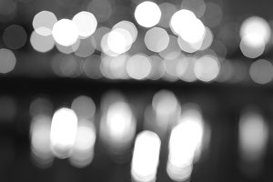 Black and white night city lights bokeh with reflections backgro