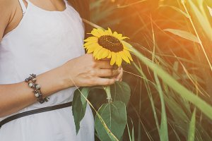 Beautiful woman holding sunflower in forest background