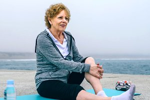 Senior sportswoman relaxing on yoga mat