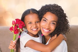 Portrait of a pretty mother sitting  with her daughter holding roses