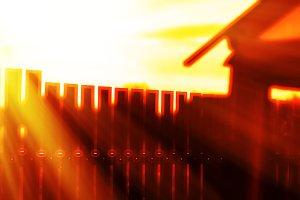 Vertical sunset fence with light leak bokeh background