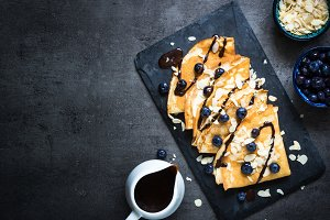 Crepes with blueberries almond flakes and chocolate sauce on bla