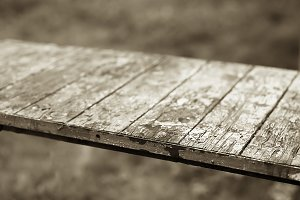 Diagonal sepia vintage wooden table bokeh background