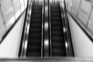 Vertical black and white motion blur airport escalator backgroun