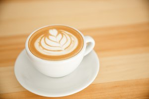 Coffee Business Concept - fresh serve hot coffee with heart latte art in modern coffee shop.