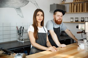 Coffee Business Concept - Positive young bearded man and beautiful attractive lady barista couple in apron looking at camera while standing at bar Couter ready to give Coffee Service at the modern coffee shop
