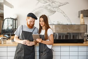 Coffee Business Concept - Cheerful baristas looking at their tablets for online orders.