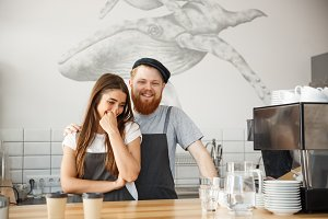 Coffee Business Concept - Positive young bearded man and beautiful attractive lady barista couple enjoy working together at the modern coffee shop