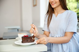Young attractive Caucasian lady enjoy eating chocolate cake with hot coffee in modern coffee shop at noon.