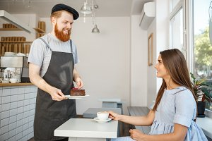 Coffee Business Concept - Waiter or bartender giving chocolate cake and talking with caucasian beautiful lady in blue dress at Coffee shop.