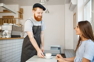 Coffee Business Concept - Waiter or bartender serving hot coffee and talking with caucasian beautiful lady in blue dress at Coffee shop.