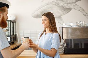 Coffee Business Concept - young smart bearded bartender enjoy talking and giving take away cup of coffee to pretty customer.
