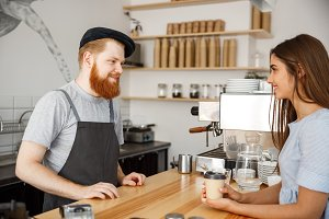 Coffee Business Concept - young beared handsome barista talking with beautiful caucasian customer in modern coffee shop.