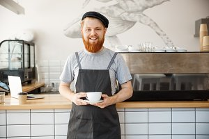 Coffee Business owner Concept - Portrait of happy  young bearded caucasian barista in apron with confident looking servicing hot coffee to customer in coffee shop counter.