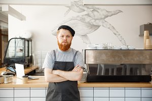 Coffee Business owner Concept - Portrait of happy young bearded caucasian barista in apron with confident looking at camera in coffee shop counter.