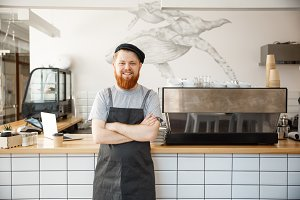 Coffee Business owner Concept - Portrait of happy  young bearded caucasian barista in apron with confident looking and smiling to camera in coffee shop counter.