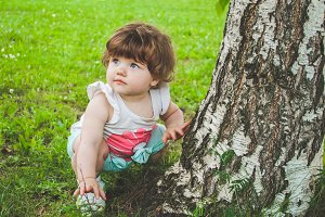 A small child sits on the grass near the tree.