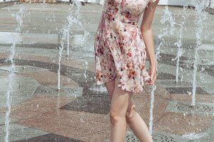 Woman is playing in the fountain with a spray.