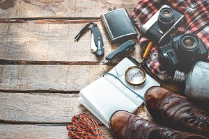 Hiking accessories on wooden background with space: old hiking leather boots, vintage film camera, maps, shirt and conserve travel Lifestyle concept adventure vacations outdoor. Flat lay top view