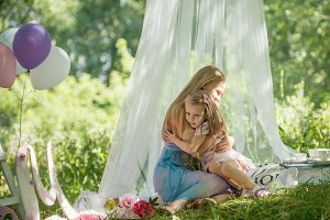 Mother and daughter is hugging in park - picnic and birthday