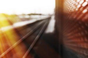 Diagonal railroad track bokeh with light leak background