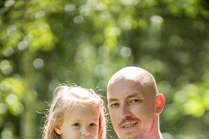 Happy family - father with daughter in summer park - vertical