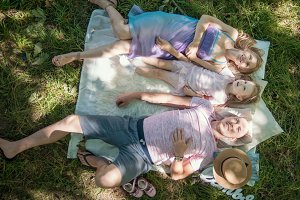 Family in park at picnic - father, mother and daughter - top view