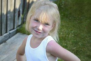 Blonde little child girl posing in countryside, summer village