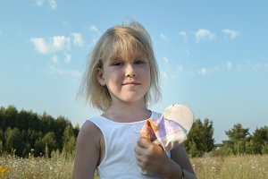 Blonde cute little child girl posing in countryside, summer village