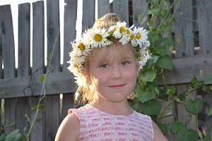 Portrait of cute little girl with flowers in hair - russian village