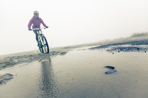Mountain Biker Racing Through Puddle