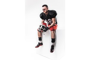 American football player sitting with  helmet on white background