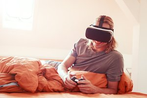 Young Man Lying On Bed, Using Vr Glasses
