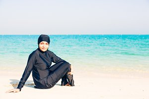Young Woman Wearing Burkini Sitting By The Beach