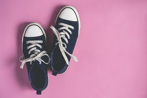 Dark blue Sneakers on pink  pastel background flat lay copy space